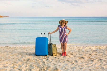 Beautiful young lady with a blue suitcase on the beach. People, travel, vacation and summer concept.