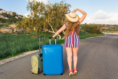 Freedom, travel, vacation and summer concept - Traveler woman with suitcases back view Foto de archivo