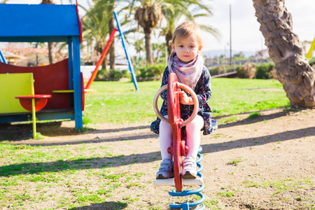 upbringing: Active little girl on playground. Little child girl