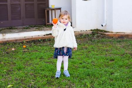 Little girl holding oranges in the garden Foto de archivo
