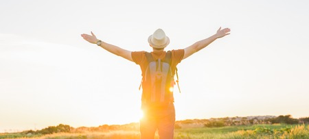 young man at sunset raises his hands up.