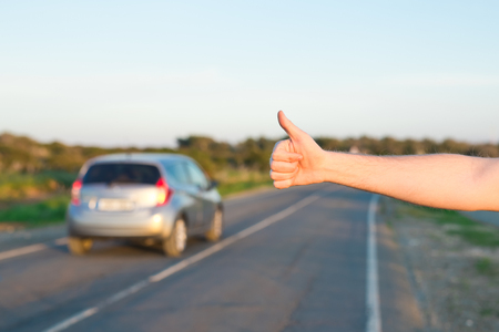 road trip, travel, gesture and people concept - man hitchhiking and stopping car with thumbs up gesture at countryside.