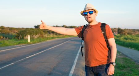 Hitchhiking traveler try to stop car on the mountain road. Foto de archivo