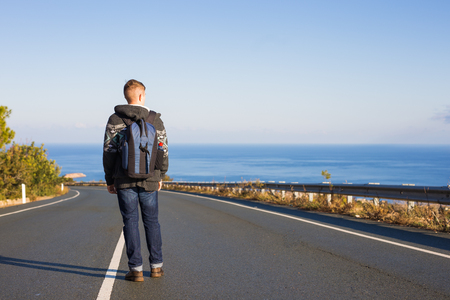 people, travel and tourism - man with backpack walks on the road