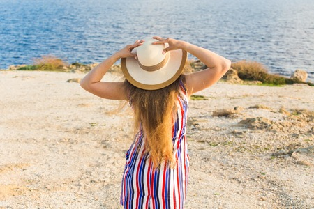 Young woman on the beach near the sea wearing dress and hat, rear view