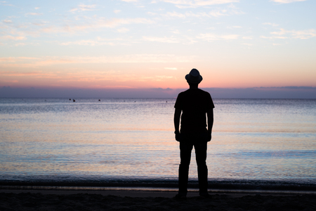 Man silhouette stand alone on stony beach and watching romantic colorful sunrise.