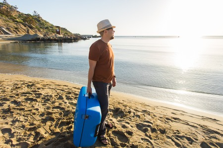 Man in sunglasses with luggage on the sea in summer sunny day Foto de archivo
