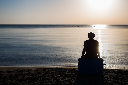Man silhouette sitting alone with suitcase on stony beach and watching romantic colorful sunrise. Foto de archivo