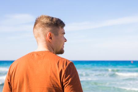 Young man relaxing on beach looking aside Foto de archivo