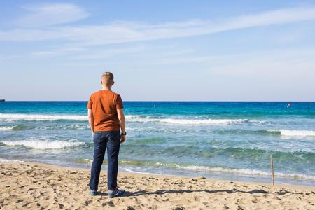 ハンサムな男が砂浜に立っています。