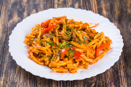 Traditional asian noodle lagman with vegetables and meat.