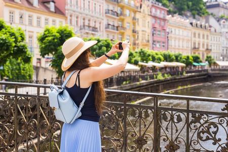 Mujer que toma cuadros con el smartphone. Elegante mujer viajero de verano en sombrero con cámara al aire libre en la ciudad europea, el casco antiguo de Karlovy Vary en el fondo, República Checa, Europa.
