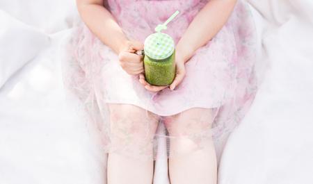 Primer plano de mujer joven celebración de batidos verdes en un picnic. Concepto de alimentos saludables, desintoxicación y dieta.
