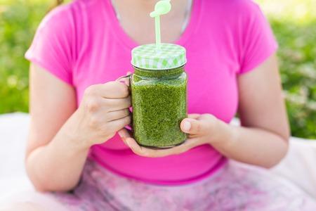 Joven mujer se divierten en el parque y beber batidos verdes en un picnic