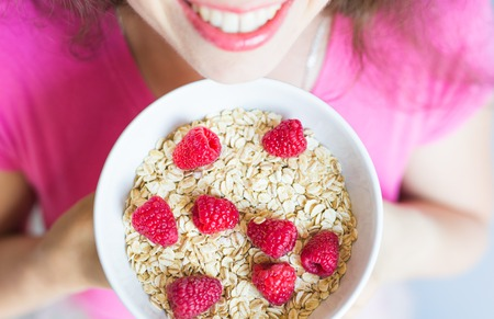 Womans hands hold healthy and natural breakfast, oatmeal and raspberries in a bowl