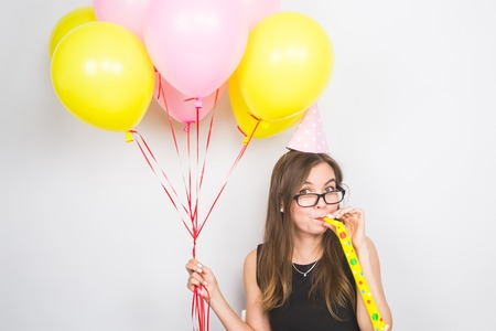 Young woman with party hat with noisemaker on a white background