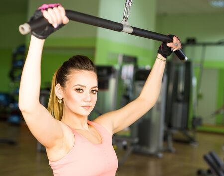 execute: beautiful muscular fit woman exercising building muscles in gym