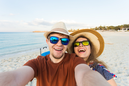 Happy young couple in love takes selfie portrait on the beach in Cyprus. Pretty tourists make funny photos for travel blog in Europe.