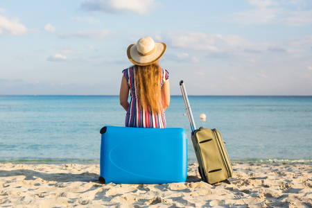 Back view of eautiful young lady with a blue suitcase on the beach. People, travel, vacation and summer concept Stock Photo