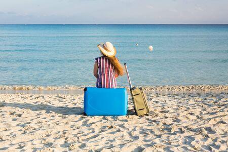 Strand, Vakantie, Vakantie en Gelukconcept - jonge vrouw dichtbij het overzees met haar bagage, achtermening Stockfoto