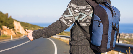hitchhiking the road. road trip, travel, gesture and people concept