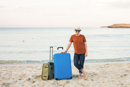 Young caucasian tourist man is standing alone on the beach with a suitcase. Stock Photo