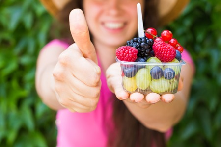Eco food and healthy lifestyle concept - Portrait of smiling woman holding berries and showing thumb up gesture Stock Photo