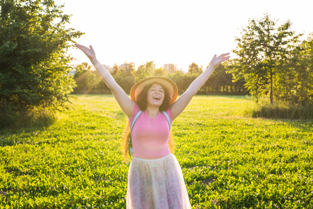 Free happy young woman raising arms watching the sun in the background at sunrise Stock Photo