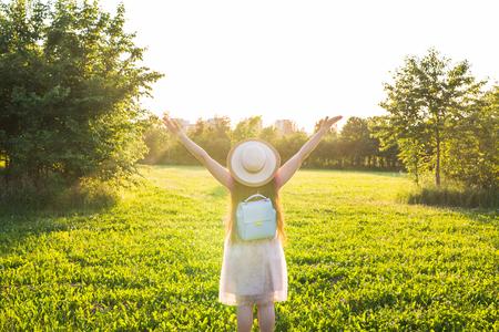 Vrije gelukkige jonge vrouw die de armen op de achtergrond bij zonsopgang op de zon schuift