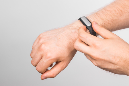 Close-up of mans hand with fitness tracker over grey background
