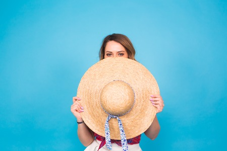 sunhat: Beautiful young woman wears in summer dress and straw hat is laughing on blue background with copy space Stock Photo