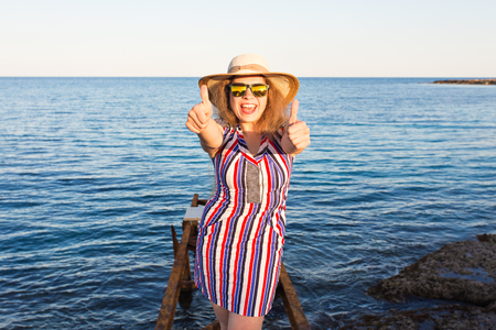 Young beautiful woman showing thumbs up on the beach Stock Photo