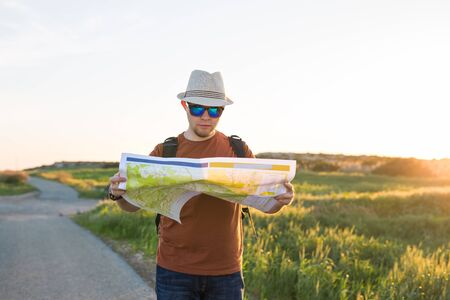 Youg man as he reads the map, traveling alone - lifestyle,people, outdoor and Holiday concept Stock Photo