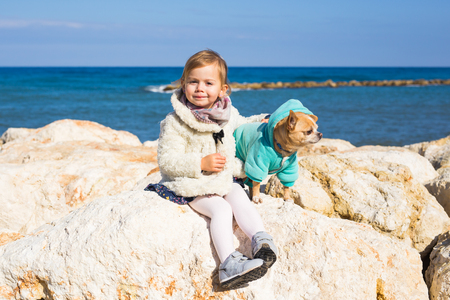 Child, pet, summer and vacation concept - Little girl with chihuahua dog on seashore
