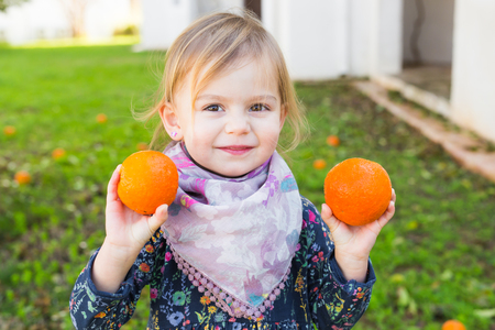 Happy laughing child playing with orange