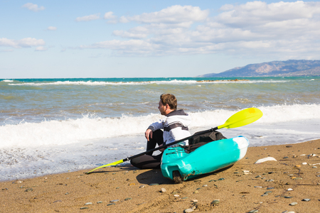 Young caucasian man sitting on beach with kayak