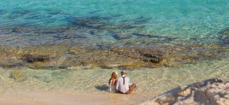 Bride and groom having fun at sandy tropical beach
