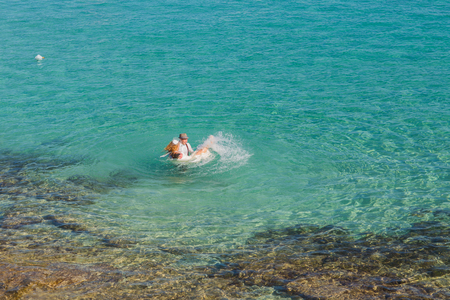 Top view of happy couple swims after wedding in turquoise sea. Romantic newly-married couple enjoying a summer vacation.