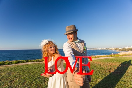 bride and groom with wooden word LOVE
