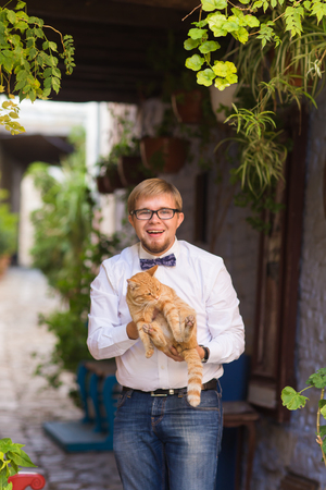 pussy: Red cat in the hands of stylish man