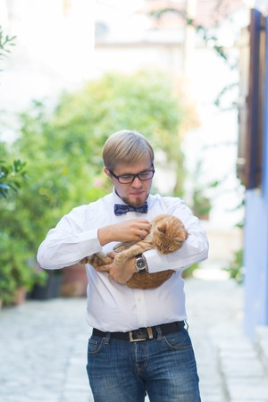 Red cat in the hands of stylish man