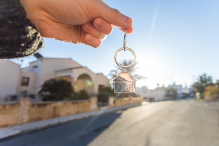 Holding house keys on house shaped keychain close up in front of a new home. Concept of real estate Stock Photo