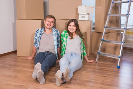 moving box: Home, people, moving and real estate concept - Portrait of happy couple in new home