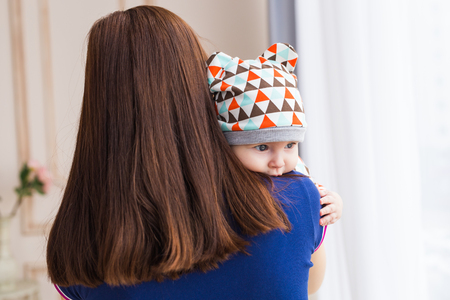 family sofa: Adorable Caucasian baby with his mother. Portrait of a three months old baby boy, back view Stock Photo
