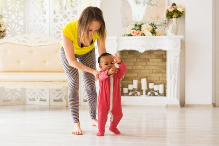 Cute little baby learning to walk, mom is holding his hands. Stock Photo