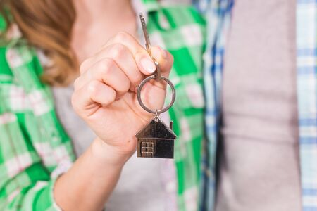 real estate sold: Female hand holding key house shaped keychain