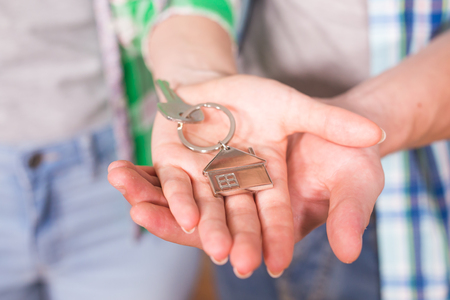 real estate sold: Holding house keys on house shaped keychain in a new home