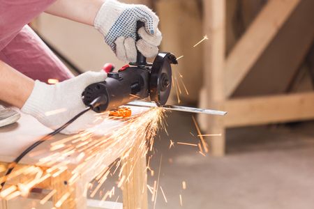 Worker Using Angle Grinder in Factory and throwing sparks