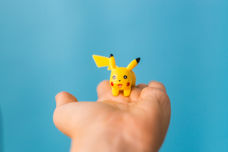 woman holding pikachu toy. pokemon go multiplayer game.