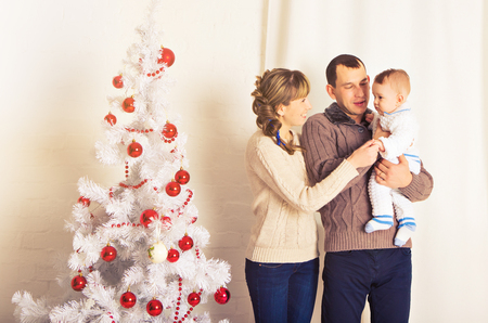 christmas, x-mas, family, people, happiness concept - happy parents playing with pretty baby boy